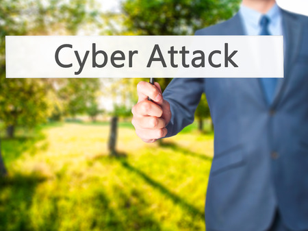 cyber war: Cyber Attack - Businessman hand holding sign. Business, technology, internet concept. Stock Photo Stock Photo