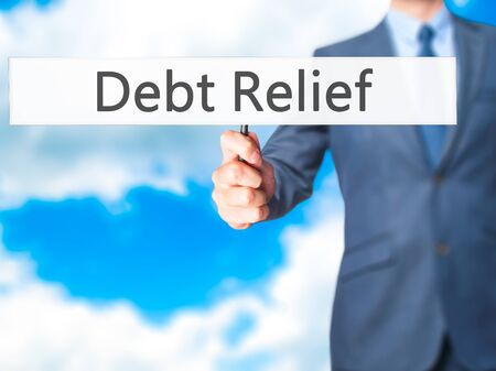 trouble free: Debt Relief - Businessman hand holding sign. Business, technology, internet concept. Stock Photo Stock Photo