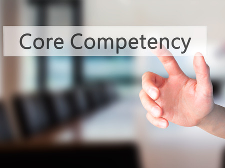competency: Core Competency - Hand pressing a button on blurred background concept . Business, technology, internet concept. Stock Photo