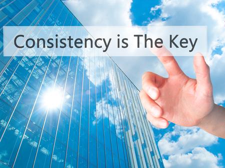 La consistencia es la clave - Mano presionando un botón en concepto de fondo borroso. Negocios, la tecnología, el concepto de internet. Foto de stock