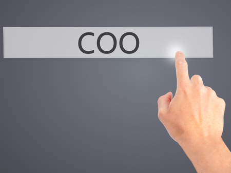 coo: COO - Hand pressing a button on blurred background concept . Business, technology, internet concept. Stock Photo