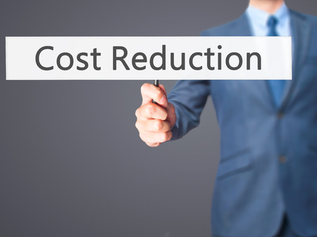 time deficit: Cost Reduction - Business man showing sign. Business, technology, internet concept. Stock Photo