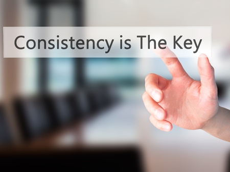 differentiate: Consistency is The Key - Hand pressing a button on blurred background concept . Business, technology, internet concept. Stock Photo