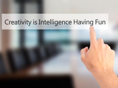 La créativité est Intelligence Having Fun - en appuyant sur un bouton sur flou fond, concept main. Affaires, technologie, internet concept. photo