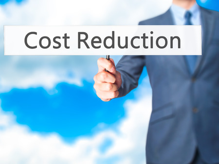 Cost Reduction - Business man showing sign. Business, technology, internet concept. Stock Photo