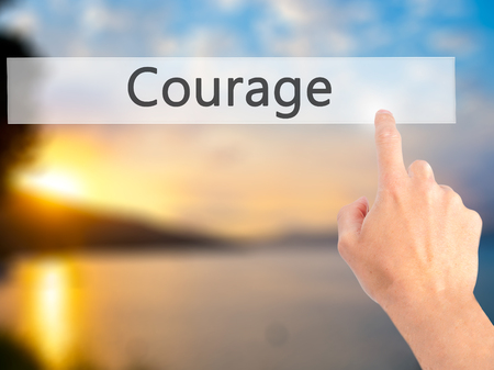 inner strength: Courage - Hand pressing a button on blurred background concept . Business, technology, internet concept. Stock Photo