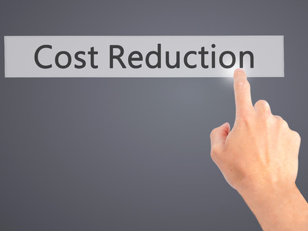cost reduction: Cost Reduction - Hand pressing a button on blurred background concept . Business, technology, internet concept. Stock Photo Stock Photo