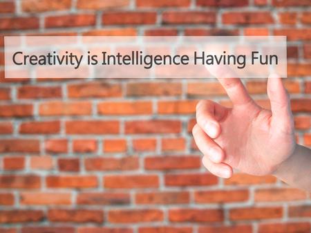 La créativité est l'intelligence de s'amuser - main en appuyant sur un bouton sur le concept d'arrière-plan flou. Affaires, technologie, concept internet. Photo Banque d'images