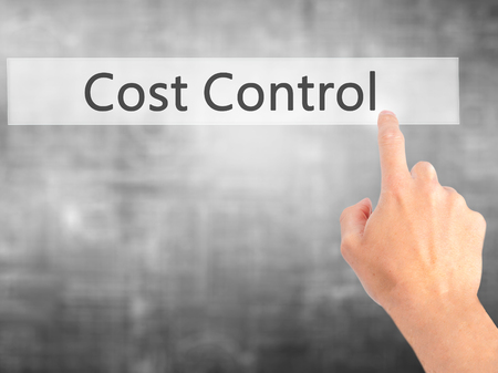 containment: Cost Control - Hand pressing a button on blurred background concept . Business, technology, internet concept. Stock Photo