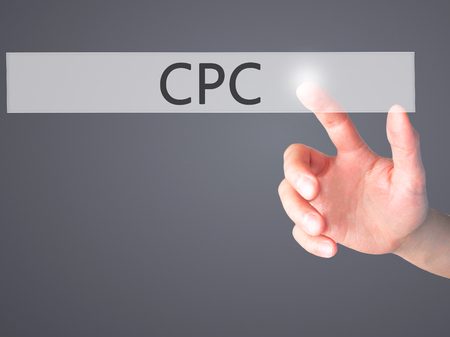 cpc: CPC - Hand pressing a button on blurred background concept . Business, technology, internet concept. Stock Photo Stock Photo