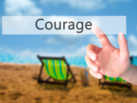 unafraid: Courage - Hand pressing a button on blurred background concept . Business, technology, internet concept. Stock Photo