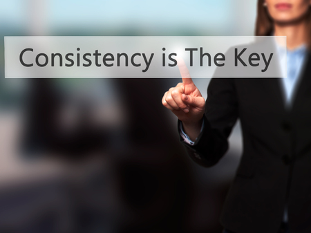 consistency: Consistency is The Key -  Successful businesswoman making use of innovative technologies and finger pressing button. Business, future and technology concept. Stock Photo