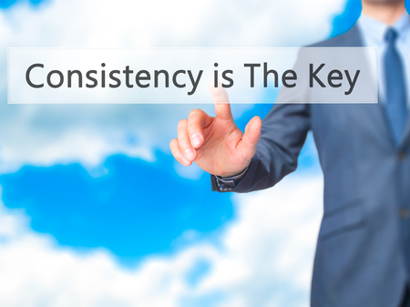 differentiate: Consistency is The Key - Businessman hand touch  button on virtual  screen interface. Business, technology concept. Stock Photo