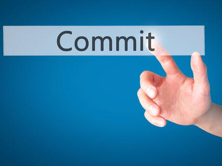 comit� d entreprise: Commit - Hand pressing a button on blurred background concept . Business, technology, internet concept. Stock Photo