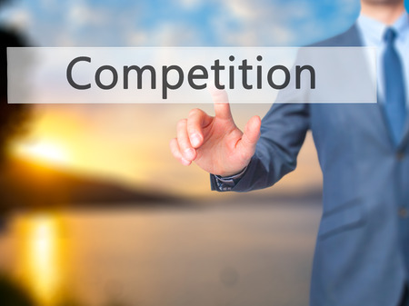 competitividad: Competition - Businessman click on virtual touchscreen. Business and IT concept. Stock Photo
