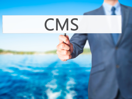 meta data: CMS - Business man showing sign. Business, technology, internet concept. Stock Photo