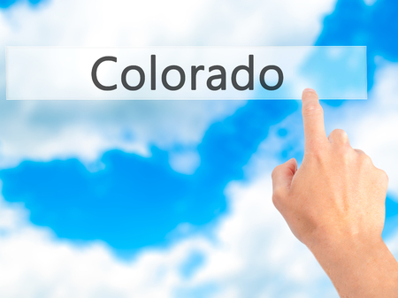 denver parks: Colorado - Hand pressing a button on blurred background concept . Business, technology, internet concept. Stock Photo
