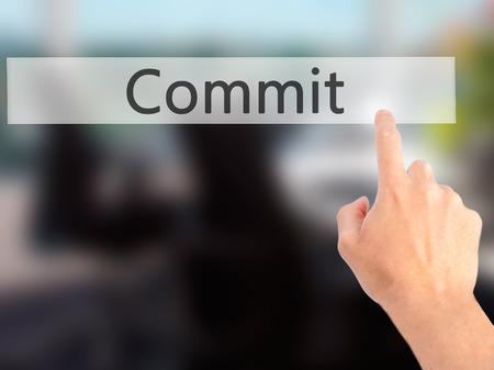 comité d entreprise: Commit - en appuyant sur un bouton sur flou fond, concept main. Affaires, technologie, internet concept. photo