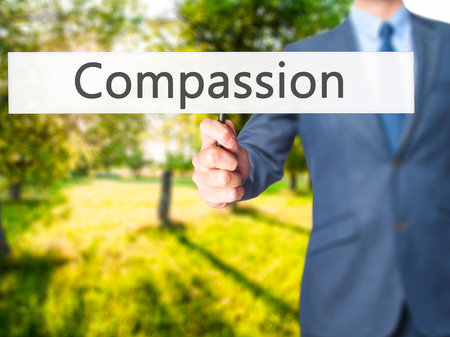 personal god: Compassion - Business man showing sign. Business, technology, internet concept. Stock Photo Stock Photo