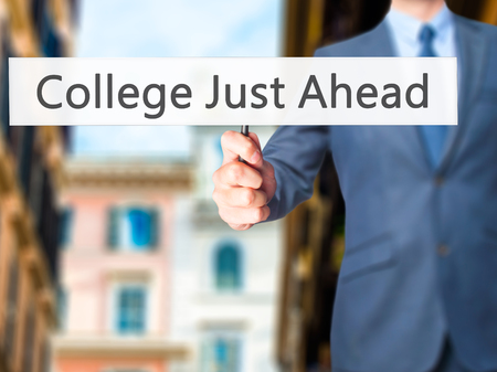 just ahead: College Just Ahead - Business man showing sign. Business, technology, internet concept. Stock Photo