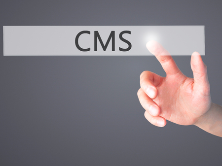 meta data: CMS - Hand pressing a button on blurred background concept . Business, technology, internet concept. Stock Photo