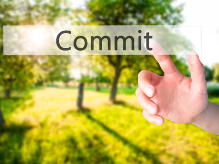 consign: Commit - Hand pressing a button on blurred background concept . Business, technology, internet concept. Stock Photo