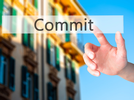 commit: Commit - Hand pressing a button on blurred background concept . Business, technology, internet concept. Stock Photo