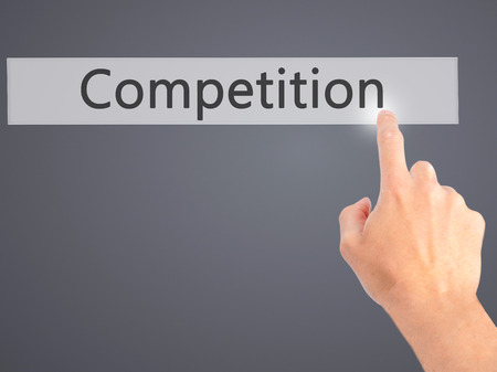 competitiveness: Competition - Hand pressing a button on blurred background concept . Business, technology, internet concept. Stock Photo