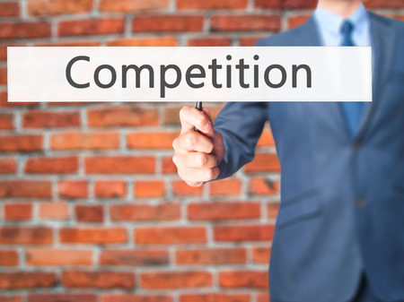 competitiveness: Competition - Business man showing sign. Business, technology, internet concept. Stock Photo
