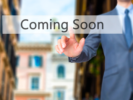 forthcoming: Coming Soon - Businessman click on virtual touchscreen. Business and IT concept. Stock Photo Stock Photo