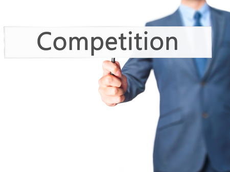 competitividad: Competition - Business man showing sign. Business, technology, internet concept. Stock Photo