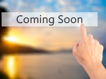 forthcoming: Coming Soon - Hand pressing a button on blurred background concept . Business, technology, internet concept. Stock Photo