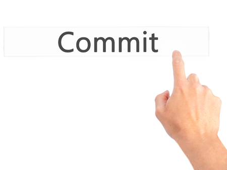 observance: Commit - Hand pressing a button on blurred background concept . Business, technology, internet concept. Stock Photo