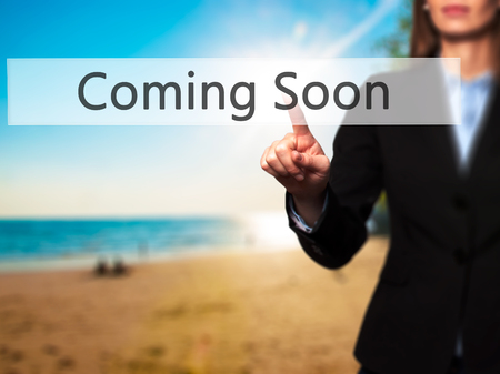forthcoming: Coming Soon -  Successful businesswoman making use of innovative technologies and finger pressing button. Business, future and technology concept. Stock Photo