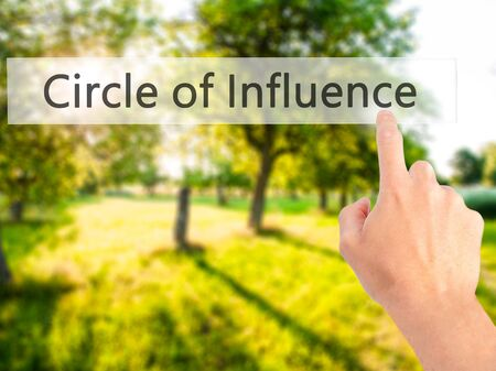 influence: Circle of Influence - Hand pressing a button on blurred background concept . Business, technology, internet concept. Stock Photo Stock Photo