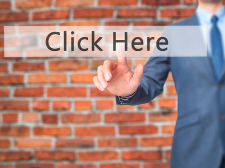 Click Here - Businessman hand pressing button on touch screen interface. Business, technology, internet concept. Stock Photo