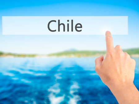 Chile - Hand pressing a button on blurred background concept . Business, technology, internet concept. Stock Photo