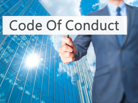 work ethic responsibilities: Code Of Conduct - Businessman hand holding sign. Business, technology, internet concept. Stock Photo