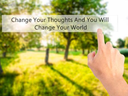 Cambiar sus pensamientos y cambiarás tu mundo - Mano presionando un botón en concepto de fondo borroso. Negocios, la tecnología, el concepto de internet. Foto de stock