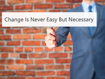 Change Is Never Easy But Necessary - Businessman hand holding sign. Business, technology, internet concept. Stock Photo
