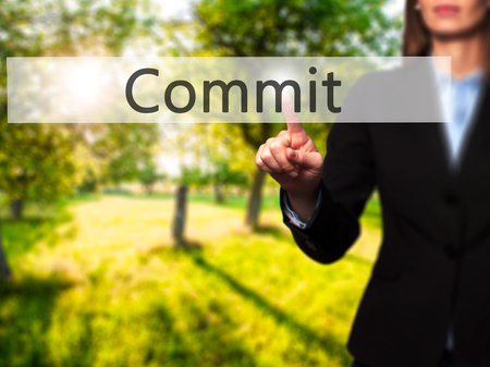 Commit -  Successful businesswoman making use of innovative technologies and finger pressing button. Business, future and technology concept. Stock Photo Stock Photo