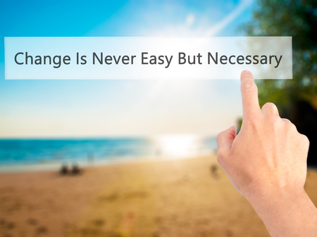 necessary: Change Is Never Easy But Necessary - Hand pressing a button on blurred background concept . Business, technology, internet concept. Stock Photo