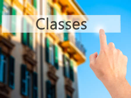 online degree: Classes - Hand pressing a button on blurred background concept . Business, technology, internet concept. Stock Photo