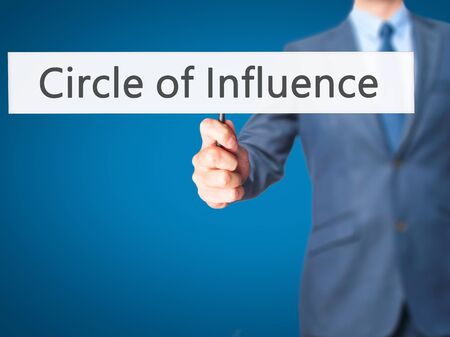 influence: Circle of Influence - Businessman hand holding sign. Business, technology, internet concept. Stock Photo
