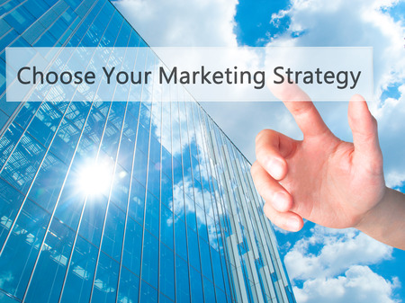 online degree: Choose Your Marketing Strategy - Hand pressing a button on blurred background concept . Business, technology, internet concept. Stock Photo