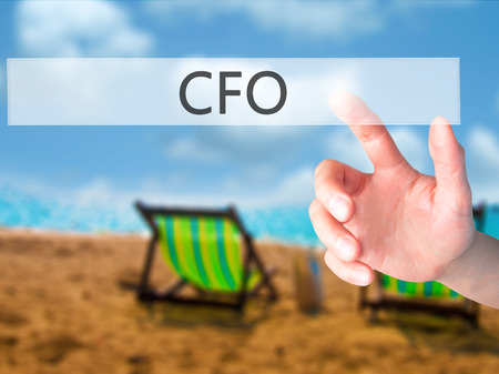 CFO (Chief Financial Officer) - Hand pressing a button on blurred background concept . Business, technology, internet concept. Stock Photo