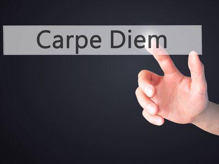 carpe diem: Carpe Diem - Hand pressing a button on blurred background concept . Business, technology, internet concept. Stock Photo