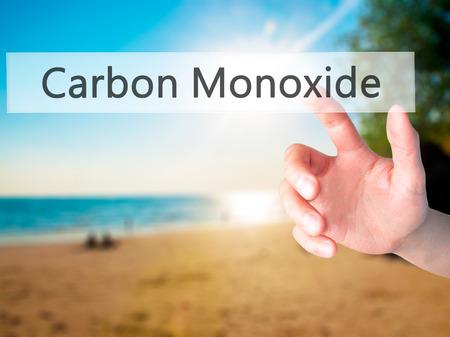 monoxide: Carbon Monoxide - Hand pressing a button on blurred background concept . Business, technology, internet concept. Stock Photo Stock Photo