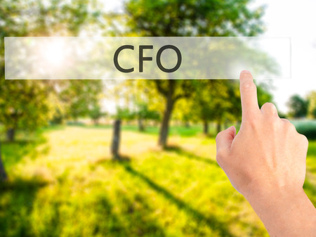 chief executive officer: CFO (Chief Financial Officer) - Hand pressing a button on blurred background concept . Business, technology, internet concept. Stock Photo