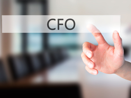 cfo: CFO (Chief Financial Officer) - Hand pressing a button on blurred background concept . Business, technology, internet concept. Stock Photo